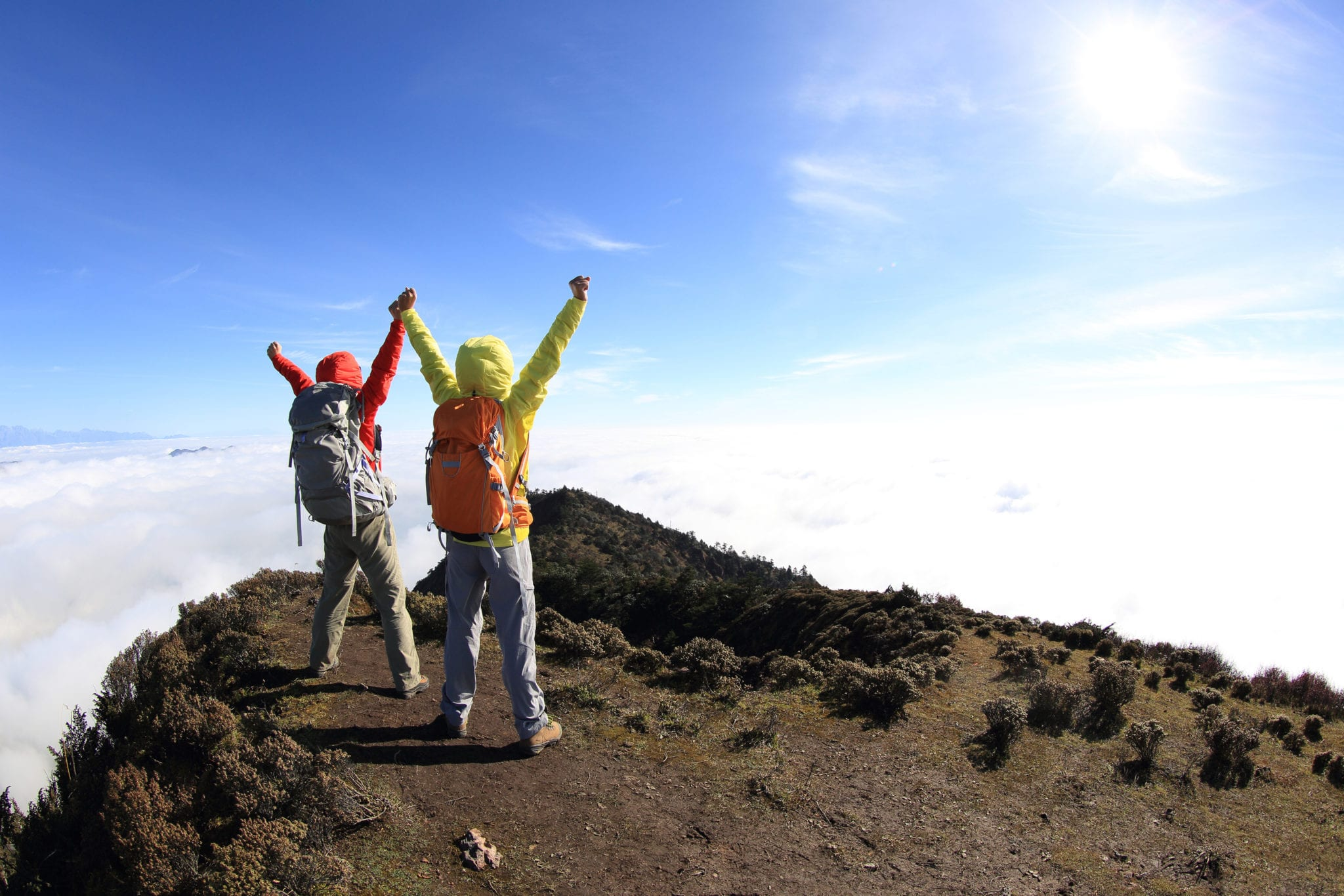 two successful  hikers cheering to sunrise on mountain peak